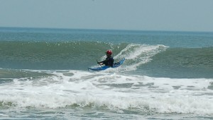 sea kayak surfing in front of the wave